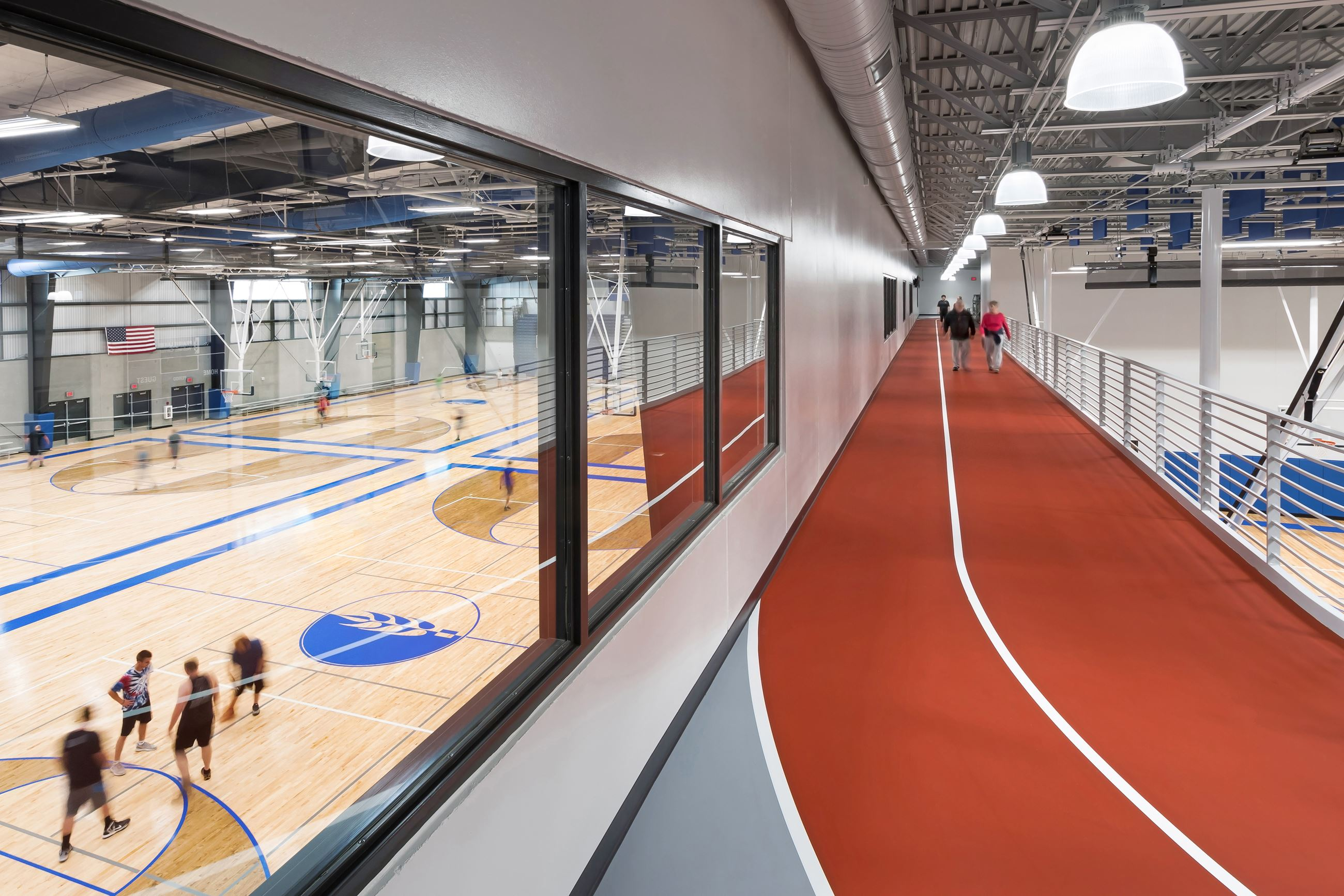 An indoor running track alongside an indoor basketball court where people are playing